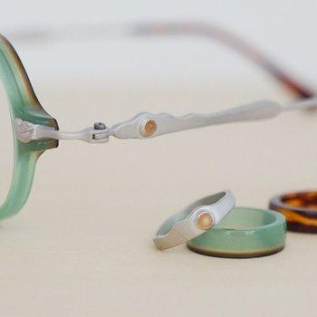 そして当時、WEBデザイナーとして働いていた夕起子さんが「本格的に彫金を始めたい」という想いがあったことなど、様々なきっかけがつながって、おふたりで眼鏡づくりをスタート。綿花由来の樹脂や、彫金の装飾パーツが織り成す、ジュエリーのような素材感の眼鏡を生み出し、注目を集めます。   メガネの職人としての技術を身に付けた泰久さん、アクセサリーが大好きな夕起子さんによる、少し異なる視点でのこだわり。「普遍性」「遊び心」のように相反しているようで、調和がとれているように感じられます。