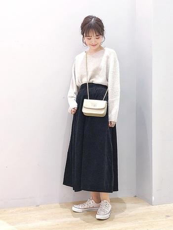レディライクな印象の黒のフレアースカートに、ふんわりニットを合わせて。足元はスニーカーではずしたら、バッグは流行りの小ぶりなものを選んで。