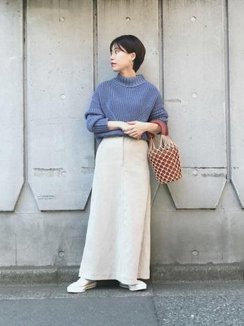 マキシロングのコーデュロイスカートは、上半身をコンパクトにまとめるのが着こなしのコツ。アクセントになる個性的なデザインのバッグを合わせて、ありきたりなコーデにならないようにします。