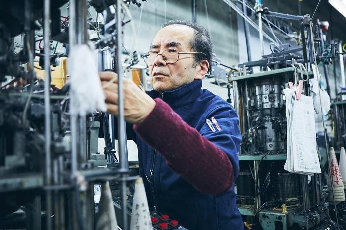 ダブル機は、複雑な編み柄を生み出すため、車輪のようなパーツを一つひとつ計算して組み合わせる熟練した技が必要。長年のキャリアを持つ職人さん。手を油で真っ黒にしながら調整が続きます