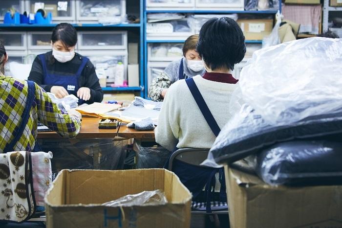 靴下の帯留めやブランド名の転写など、出荷に向けて作業するニット・ウィンの方々