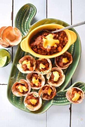 メキシコ料理のナチョスを餃子の皮で作るレシピ。餃子の皮をマフィンカップの形に合わせて、パリパリになるまでトースターで焼きます。チリビーンズとチーズを乗せたら完成!