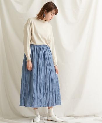 ナチュラルなシワ加工が素敵なスカート。白のアイテムと合わせて、清潔感がありつつも肩の力の抜けたコーデに仕上がっています。