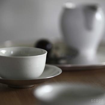 長崎県波佐見町で生産されている東屋の汲み出し湯呑です。 湯呑みの肌は自然な雑味があり、それがまたお茶の色を引き立ててくれます。素朴が一番、ということが身にしみる茶器。  茶托の材質は銅です。銅の生地の上から錫めっきが施されおり、経年変化でより素敵に輝きます。
