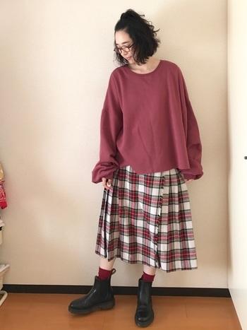 スウェットとスカートをくすみレッドでカラーリンク。ブーツからソックスを覗かせる小技も効いています。