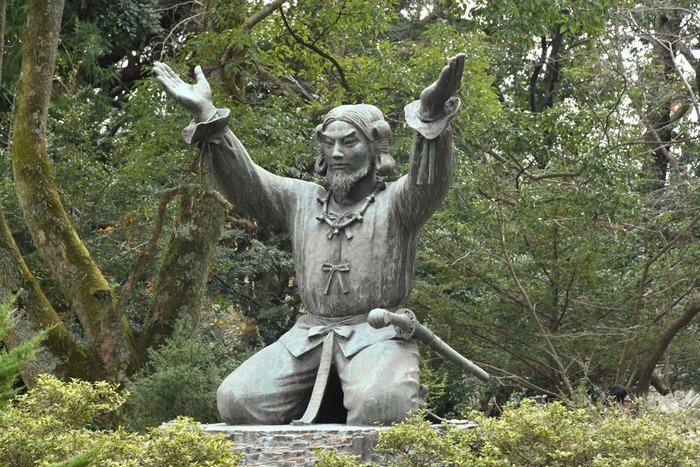 """出雲大社で参拝をしたら、ぜひ足を運びたいのが、銅鳥居前にある「ムスビの御神像」です。 大国主大神が、修行の身であるころ。海からやってきた「幸魂奇魂(さきみたまくしみたま)」という魂から """"おかげ"""" をいただき、神性を養われ「ムスビの大神」になられたのだとか。"""