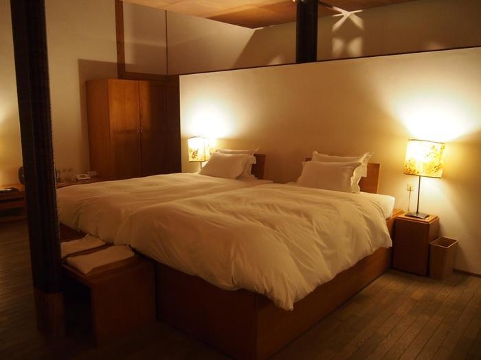 ゆとりのある大きめのベッドで心も体もゆっくりと休まりそうですね。木のぬくもりが感じられてくつろげる空間です。