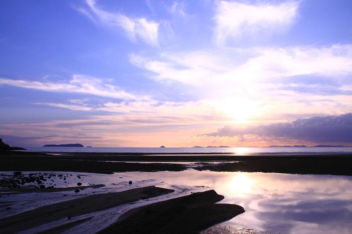口コミやSNSで「日本のウユニ塩湖」と話題を呼んでいる香川県三豊市にある「父母ヶ浜(ちちぶがはま)海岸」です。ウユニ塩湖とは、南米ボリビアにある湖で、湖面に空を映し出す「天空の鏡」と言われている絶景スポット。ここ「父母ヶ浜海岸」も満ち潮や引き潮で運ばれてきた砂が溜まって遠浅になることで、干潮時に大きな干潟と潮溜まりができ、このような美しい現象に出合うことができます。西向きの海岸なので、日没時のオレンジ色の夕景はさらにロマンチックで日本にいることを忘れそう。