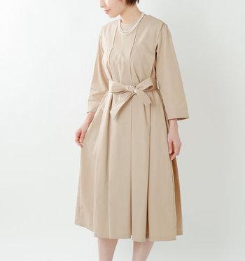 全体にたっぷりとタックを入れ、エレガントな雰囲気に仕上げて。裾に向かってふんわりと広がるシルエットが、大人の女性の品格を引き立てます。共生地のリボン付きで、ウエストマークして着用すればメリハリの効いたシルエットも楽しめますよ。