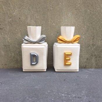イニシャルとリボン部分がアクセントカラーで仕上げられた香水瓶。中の見えないボトルも、インテリア雑貨のようで新鮮ですね。