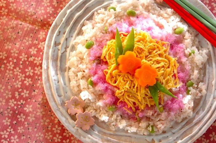 桜の花を思わせる食卓を美しく彩る桜のちらし寿司。 ご飯には、すし酢、枝豆、桜の塩漬けが入っています。盛り付けは、桜でんぶ、錦糸卵、きぬさやをバランスよく…。仕上げに桜をかたどったにんじんで華やかさをさらにUP!