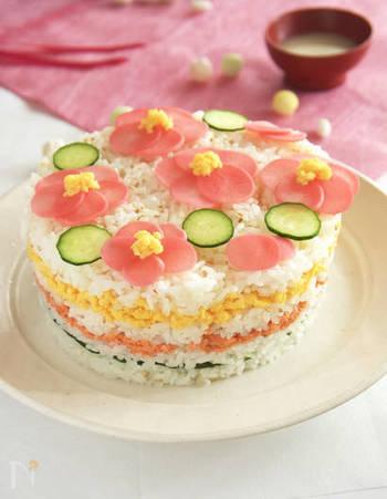 女の子が喜ぶこと間違いなしのひな祭りのケーキ寿司。 3段のそれぞれの間にはキュウリ、鮭、卵がサンドされています。一番上に飾られたお花はラディッシュで作られたもの。酢漬けにすることにより、自然にピンク色に発色します。