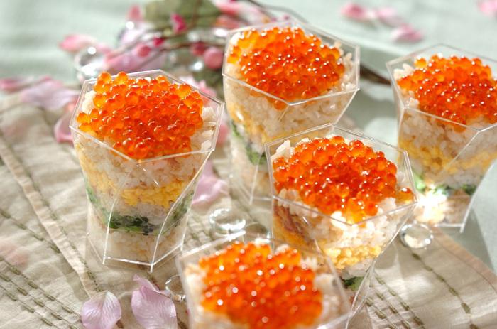 春の訪れを感じることが出来る、菜の花が入ったカップ寿司。 間にサンドしているのは、特性のツナそぼろ、炒り卵、菜の花の塩ゆで。断面が美しく引き立つよう透明な器に盛り付ければ、より食卓が華やかに…。一人づつ取り分けなくても、そのまま食べられるので、パーティーシーンにぴったりです。