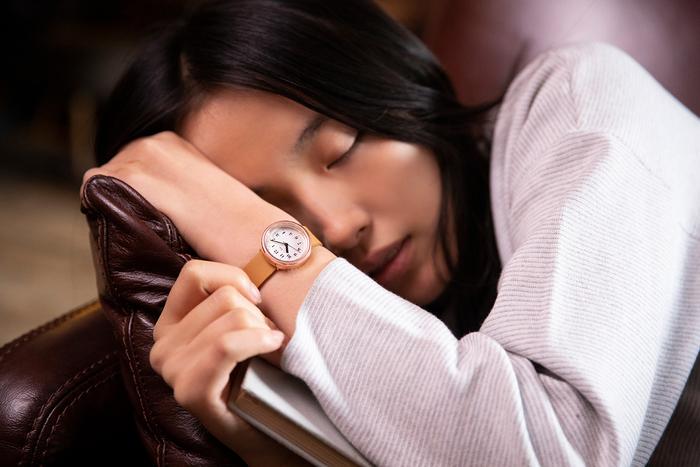 春眠暁を覚えず――本を読んでいたら、つい眠り込んでしまうときもあります。ピンクゴールドのメタルはやさしく輝き、ベージュのベルトとの組み合わせがとてもナチュラルな印象。肌馴染みがよくて、リラックスしているひとときに寄り添ってくれるようです。チクタクと時を刻む秒針も、心地よいリズムに。