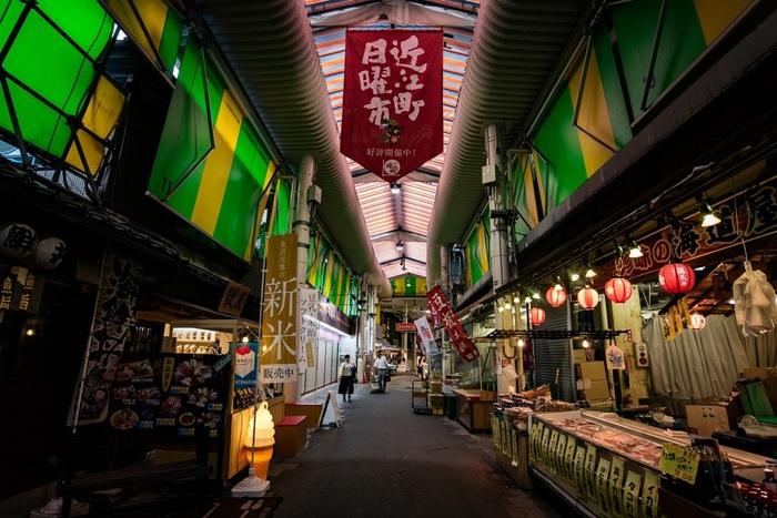 """「近江町市場」は、金沢駅から徒歩約15分のところにあるスポットです。「兼六園」や「金沢21世紀美術館」からも徒歩15分以内で行けますので、周辺観光の合間に立ち寄るのも良いでしょう。  「近江町市場」の歴史は古く、なんと300年近くも""""金沢の台所""""として人々に親しまれてきたというから驚き。新鮮な野菜や果物、魚介、お肉などさまざまな食材が手に入るだけでなく、おいしいお寿司さんなどの飲食店も充実しているので、お腹が空いたときはぜひ足を運んでみて。"""
