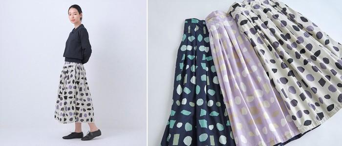 """新作のテキスタイルは画家の小川温子さんが描いた図案を基に作られたオリジナルプリント。 3柄にはそれぞれテーマがあり、ネイビーは""""宝石のカケラ""""、パープルは""""貝殻のカケラ""""、ベージュは""""砂のカケラ・石のカケラ""""をイメージしているのだそう。 「チノプリーツスカート」と同じ形ですが、生地はコットン100%のやわらかい素材を使用しており、よりふんわりとした印象の春夏向きの「タックスカート」になります。"""