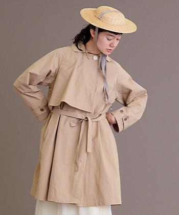 使いやすい膝上丈のトレンチコートは、パンツはもちろんバランス調節が難しいミモレ丈スカートとも好相性。首元の大きめボタンと、ケープを思わせるフロントの重なりがポイントです。