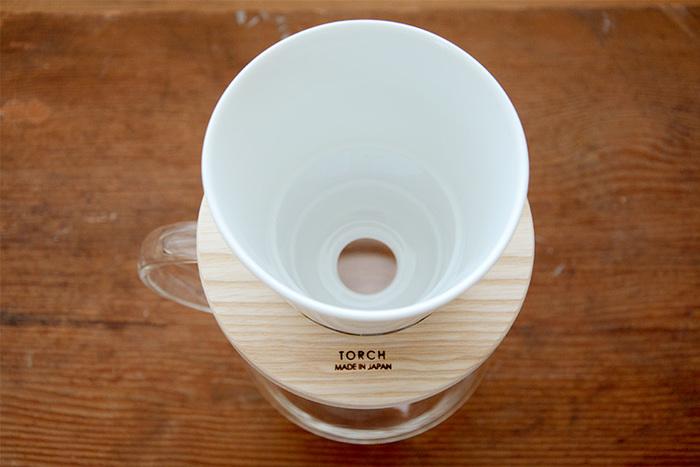"""磁器製のドリッパーに、ホワイトアッシュの無垢材を使った""""ドーナツドリッパー""""。コーヒー好きが高じて、理想のドリッパーを作ってしまったという「TORCH(トーチ)」の中林孝之さんが手がけたこのアイテム。 縦に長細い形なので、お湯を注ぐと、より多くのコーヒー粉を伝って抽出されます。いつものコーヒーをもっと美味しくしたいという人に贈ってみてはいかがでしょう。"""