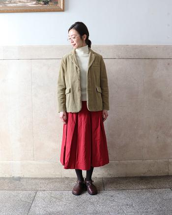 ハッと目をひく情熱的な赤いロングスカートはジャケットを合わせて優等生風に。