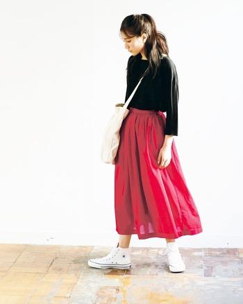 真っ赤なロングスカートにはブラックを合わせてきりりと着こなしたい。足元は優しいニュアンスのコンバースのハイカットをチョイス。