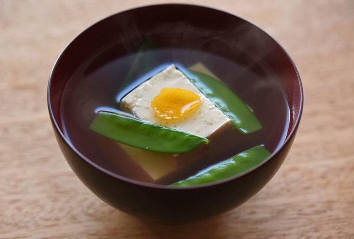 豆腐と絹さやだけでできるだけシンプルなお吸い物。見栄えよく仕上げるポイントは、お椀に盛り付ける際に、豆腐だけを先に、下2つ、上1つに重ねて盛りつけること。仕上げにユズの皮を添えればより、香りも見た目もアップして◎。