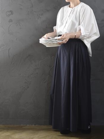 ゆったりとしたサイズ感のポンチョブラウスは、フロントだけをタックインするスタイリングでスッキリとコーディネート。ダークトーンのロングスカートを合わせて、大人モノトーンコーデの完成です。