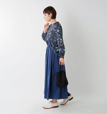 リバティプリントを採用した、ネイビーの花柄ブラウス。ブルーのロングスカートを合わせて、同系色でまとめています。足元の白シューズと、花柄デザインで女性らしい明るさをプラス。