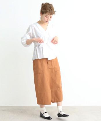 ウエストに大きなリボンがあしらわれた白ブラウスは、テラコッタ系のタイトスカートを合わせてスパイシーさをプラス。甘さ控えめの着こなしになるよう、大人っぽさを意識したコーディネートに仕上げています。