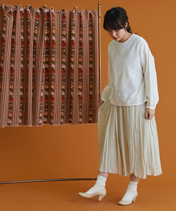 フロント全面に刺繍を施した白ブラウスは、ワントーンコーデで清楚な印象に。ベージュのパンプスに合わせた白ソックスは、くしゅっとさせて肌をちら見せしているのもポイントです。