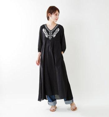 マキシ丈ワンピースの胸元に、ふんだんに刺繍をあしらった民族チックな黒ワンピース。フェミニンな着こなしも素敵ですが、あえてデニムパンツを合わせて、上手にカジュアルダウンしています。