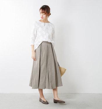 花の刺繍を施した白ブラウスに、グレーのプリーツスカートを合わせたスタイリングです。ベーシックな大人コーディネートなので、羽織や小物などのテイストを選ばないのが魅力ですね。