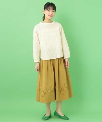 ベージュのフレアスカートに、サークル柄の刺繍がとってもキュートな一枚。白の透け感ブラウスとグリーンのパンプスを合わせて、レトロ感のあるコーディネートに。