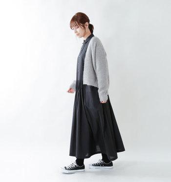 ふわっと広がるフレアシルエットが、女性らしい印象を与える黒のシャツワンピース。グレーのニットカーディガンを羽織って、足元はスニーカーで上手にカジュアルダウンしています。