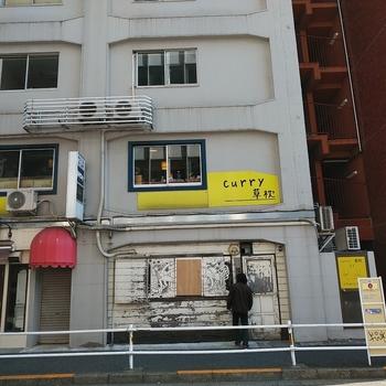 都営新宿線の新宿三丁目駅を出てすぐの雑居ビルにある「curry 草枕」は、ちょっと分かりづらい場所にありますが、ランチタイムは行列ができる人気店。黄色い看板が目印ですよ。
