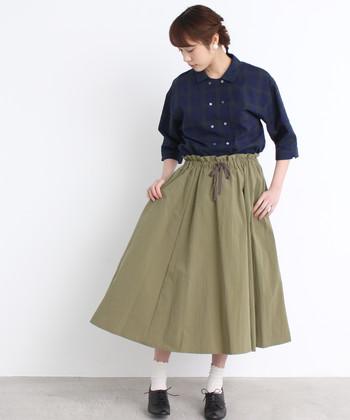 ボリューム感のあるカーキのロングフレアスカートは、ネイビーのシャツをタックインしたスタイリングに。ウエストデザインをしっかり見せることでおしゃれ度がグッと上がります。