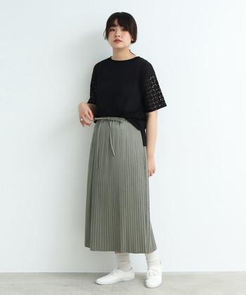 ちょっぴりくすみ感のあるカーキのプリーツスカートに、黒の半袖トップスをタックインしたスタイリング。足元は白の靴下とシューズを合わせて、明るさをプラスしています。