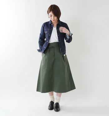 ハイウエストデザインのカーキロングスカートは、裾に向かってパリッと広がるフレアシルエットがクールな印象。白トップスとデニムジャケットで、ハンサムコーデに仕上げています。