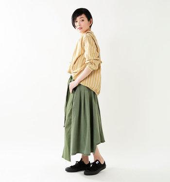 スウェーデン軍のミリタリーパンツを解体し、アシンメトリーデザインのスカートにリメイクしたこちらのアイテム。ベージュのストライプシャツに合わせて、メンズライクな雰囲気にきちんと感を添えたコーディネートの完成です。