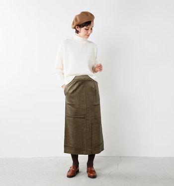 コーデュロイ素材のカーキロングスカートは、着痩せ効果も期待できるタイトスカートをチョイス。白のハイネックニットを合わせて、フロントをちょこんとタックインしています。季節感のあるベレー帽もプラスして、ナチュラルな秋冬コーデの完成です。