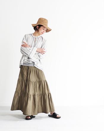 ボリューム感たっぷりで甘めな印象になりがちのティアードスカートも、カーキのロングスカートを選べばかっこよくキマります。ストライプブラウスから、グレーのインナーをちら見せしているのもポイント。