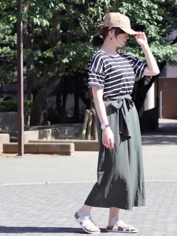 大きめのウエストリボンが印象的な、「GU(ジーユー)」のカーキロングスカート。ボーダートップスとベージュのキャップを合わせて、トレンドのスポーツミックススタイルに仕上げています。