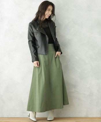 マキシ丈のカーキロングスカートは、女性らしいフレアシルエットをチョイス。黒トップスと黒のレザージャケットで、辛口スタイルに仕上げています。足元は白のブーツでほんのり柔らかさをプラス。