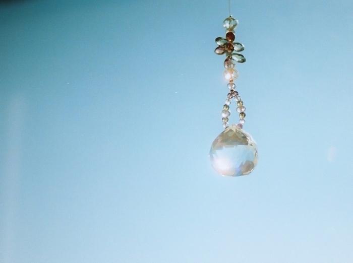 窓辺に数cm程度のクリスタルガラスをカットしたものを、紐やワイヤーなどで吊るし、太陽の光を投映し、その光の輝きを楽しむインテリアアイテム「サンキャッチャー (Suncatcher)」。