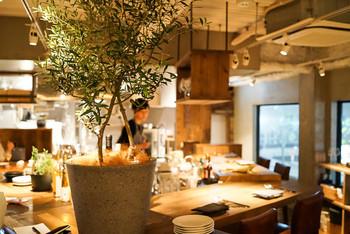 店内に入ると、コの字型のカウンター席にテーブルが数席あります。木のぬくもりが感じられ、全体的に落ち着いている印象です。シェフが真ん中にいて、おしゃべりをしながら食事ができる、非常にカジュアルで珍しいタイプのイタリアンです。