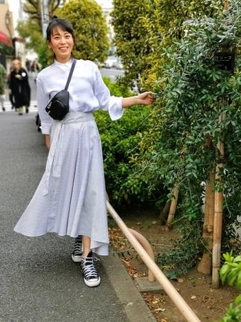 しっかりボタンを留めた白シャツにフレアのロングスカートを合わせたMIXコーデ。白とグレーの組み合わせで、春らしい明るい色合いのスタイリングです。足元はスニーカーではずし、たくさん歩く日曜日のお出かけもバッチリです。