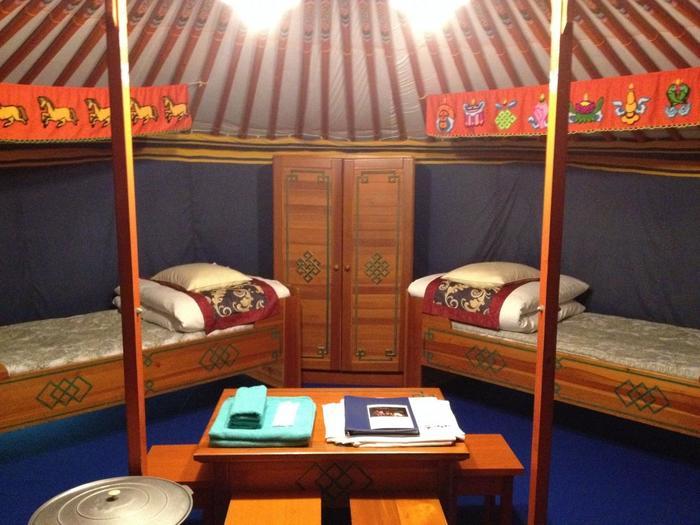 """ゲルの中は、最大で6人まで泊まれる広さ(2人分は敷布団が用意されるそうです)。ベットは4つ用意されていて、家具やベットもモンゴル仕様で、モンゴルから直輸入しているんだとか!テレビやエアコンもきちんと完備されているので、小さなお子さま連れにも安心。非日常な空間に泊まる体験は、きっと、心に残る良い思い出に…。 お友達と、家族と、恋人と…是非、""""ゲル""""での宿泊を楽しんでみてはいかがでしょうか♪"""