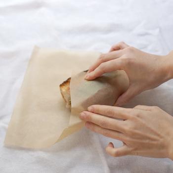 バゲットサンドやロールパンサンドなどの丸みのあるパンもワックスペーパーで包むことができます。ワックスペーパーの中央に向きを傾けて置き、紙の角からプレゼントのラッピングのように包んでいけばOK。