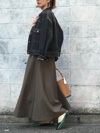 オーバーサイズの黒デニムジャケットを肩にかける着こなしも女性らしさを引き立てます。ロングのフレアスカートと合わせて甘辛テイストを楽しみましょう。