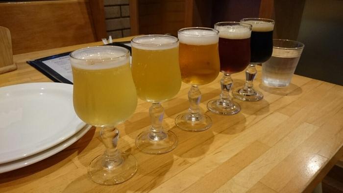 是非こちらを訪れた際おすすめなのが、5種類のクラフトビールが100mlずつグラスに入った「お試しセット」。 小さめのグラスに色の違うビールが5種類、たっぷりと注がれています。それぞれのビールに特徴や個性があり、この飲み比べはビール好きにはたまらないですね!ビールに良く合うウィンナーや、ピザ、パスタなどのお食事メニューも豊富に用意されているので、お腹も大満足です。