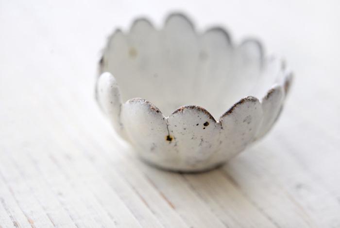 ぱっと花が咲いたような可憐なデザインと、直径約5.5cmの小ぶりのサイズ感が可愛い村上 直子(むらかみ なおこ)さんの「マーガレット豆鉢」です。ちょっとしたおつまみや薬味、ソース入れにぴったりの豆鉢は、単品使いはもちろんのことワンプレートの小鉢にも◎。温かみのある素朴な風合いと、グレーがかったような優しい色合いの「白」も印象的です。